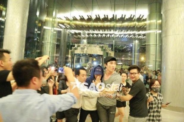 Quản lý của EXO ôm trọn Xiumin để bảo vệ anh trước vòng vây fan Hà Nội.