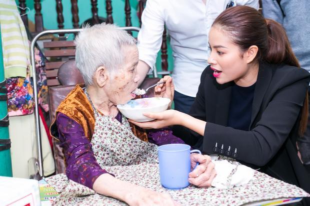 Hoa hậu Hoàn vũ Việt Nam 2015nhiệt tình bón cơm cho một cụ bà. Phạm Hương cho biết, cô thương các cụ như bà ngoại mình và rất xúc động khi nghe các cụ kể về những hy sinh, mất mát trong chiến tranh.
