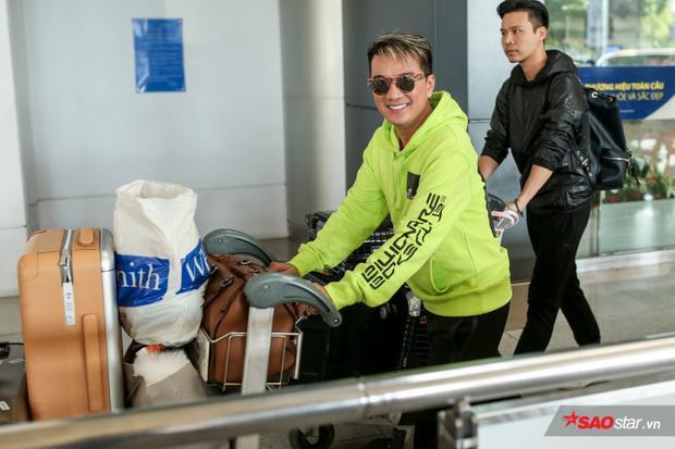 Nam ca sĩ diện áo xanh nổi bật, tự đẩy hành lý ra xe. Anh bất ngờ trước sự chào đón nồng nhiệt từ người hâm mộ.