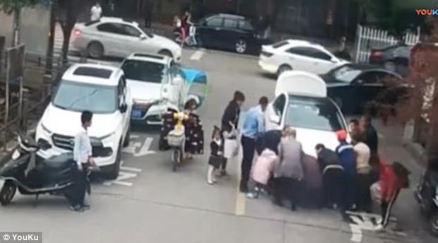 Người qua đường giúp Pan nâng xe cứu cậu bé.