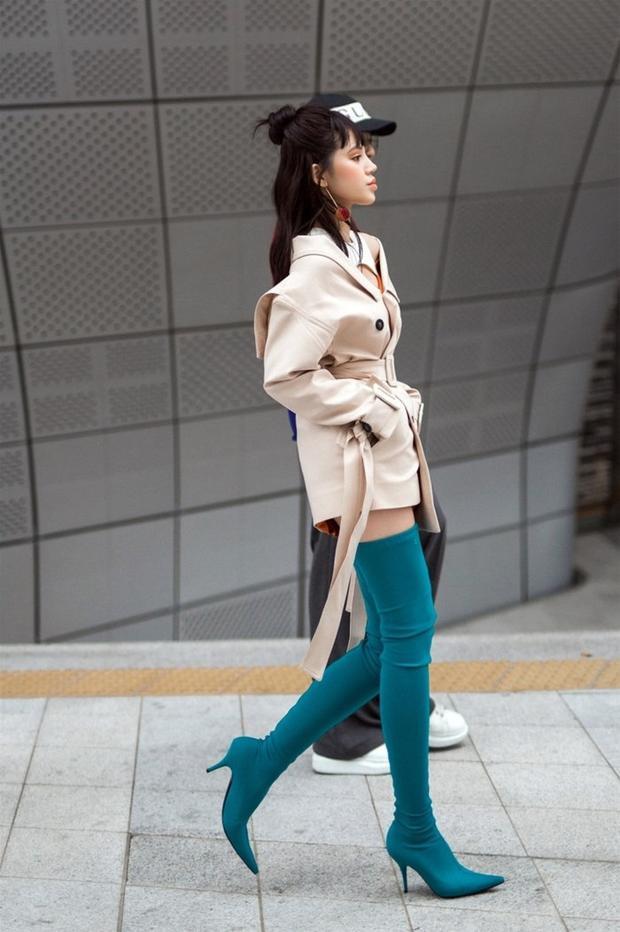 Trong một set đồ khác, Jolie Nguyễn sử dụng đôi bốt màu xanh lam lạ mắt, kết hợp cùng áo khoác màu beige giúp phần nhìn dịu mắt hơn.