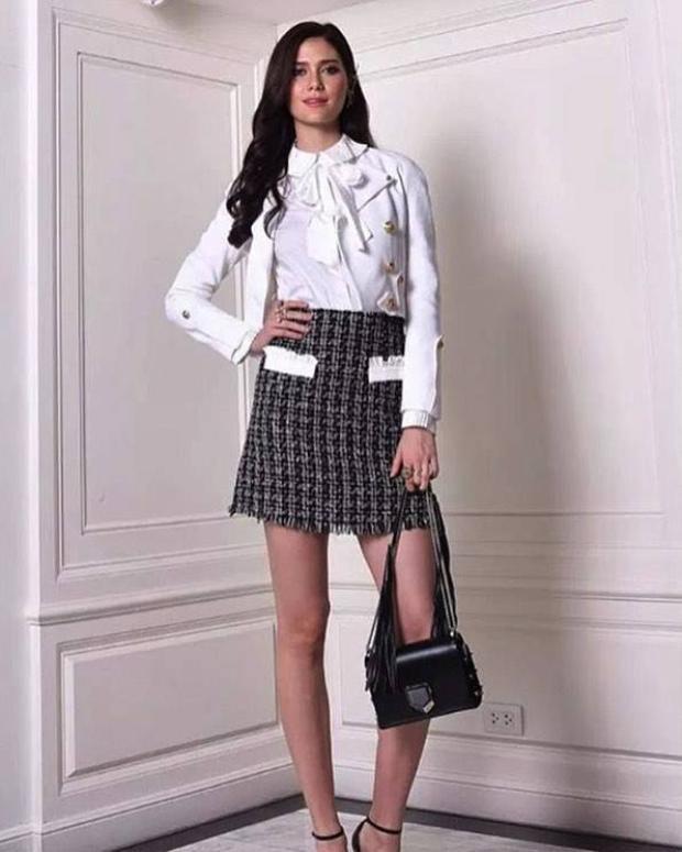 Sơmi lụa trắng kết hợp cùng chân váy caro, clutch da đi kèm hoàn thiện bộ cánh cách tinh tế.