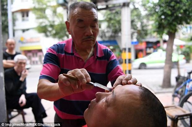 Ông Xiong Gauwu đang lấy gỉ mắt cho khách bằng dao cạo.