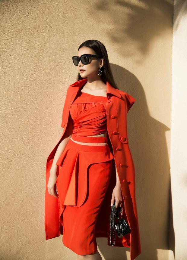Tông màu cam đỏ cũng là một gam màu yêu thích của Thanh Hằng, bộ váy được cắt may tinh tế với kỹ thuật draping ôm sát cơ thể, giúp cô khoe số đo hình thể. Siêu mẫu cũngkhéo léo kết hợp cùng chiếc túi xách nhỏ và mắt kính đen độc đáo để tạo độ tương phản.