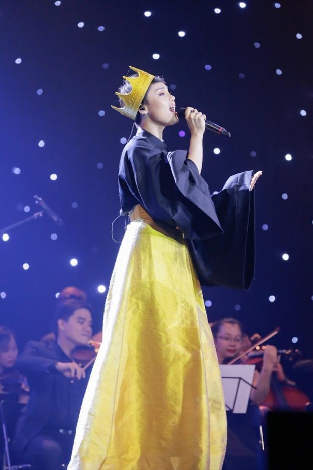 """Đây là bộ cánh mà Miu Lê xuất hiện trong tập 1 """"Sao đại chiến"""". Cô đội vương miện vàng, áo sơ mi đen cách điệu lượt thượt và chân váy vàng chói lòa sân khấu."""