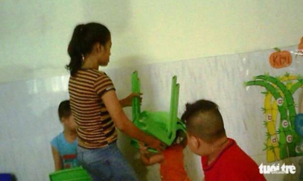Một bảo mẫu dùng ghế nhựa đè lên đầu trẻ em tại trường mầm non thư thục Mầm Xanh, Q.12. Ảnh: Báo Tuổi Trẻ