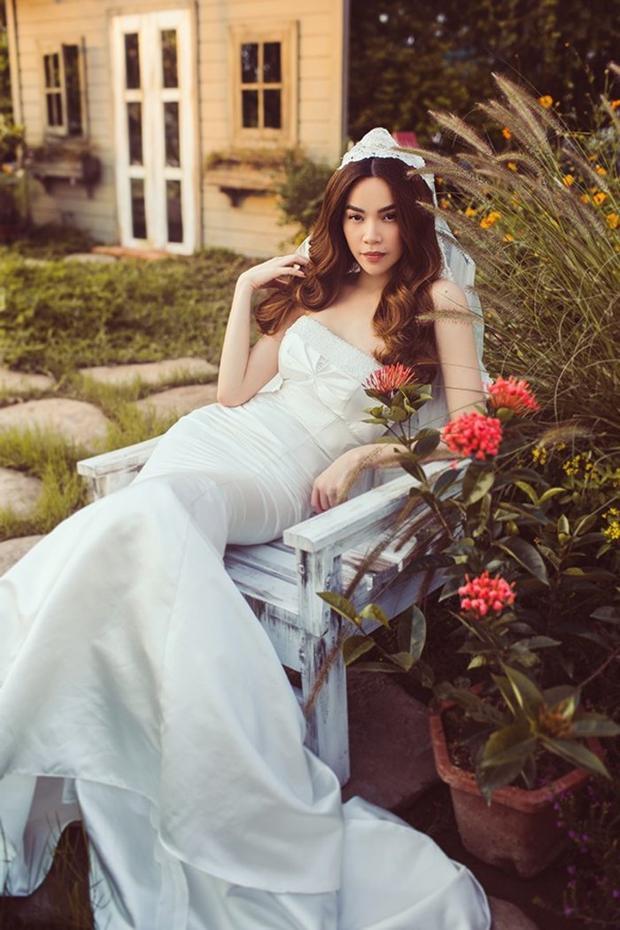 Trong trang phục váy cưới sắc trắng, Hà Hồ chọn kiểu tóc xoăn lô màu nâu sang trọng.