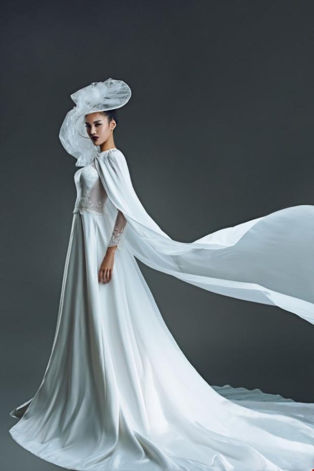 Trái ngược, vvới mẫu áo dài cưới cổ điển nhưng được biến tấu thêm áo choàng dài này, Lan Khuê đẹp một cách kín đáo nhưng đầy quyền lực.