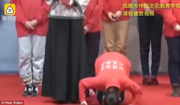 Nữ học sinh quỳ gối, cúi lạy trước camera.