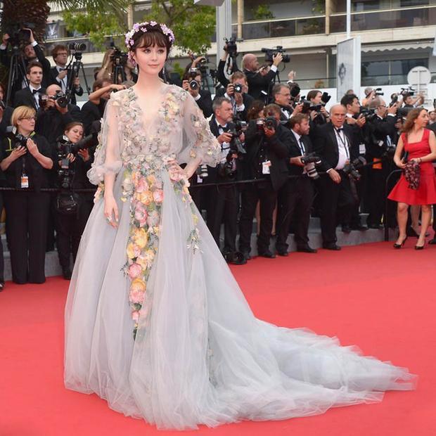 """Đây là bộ đầm dạ hội được thiết kế với phần cổ V xẻ sâu quyến rũ, đính hoa 3D kỳ công. Nói không ngoa, Phạm Băng Băng trở thành """"Nữ thần hoa"""" đích thực trên thảm đỏ Cannes trong trang phục này. Năm 2017, người đẹp nhiều lần xuất hiện với váy hoa phong cách đa dạng. Trong ảnh, nữ diễn viên khoe sắc với thiết kế xuyên thấu của NTK Christopher Bu."""
