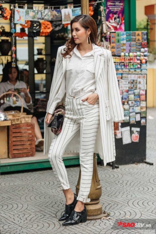Vest trắng sọc dọc giúp Minh Tú vốn sở hữu đôi chân đã dài lại càng dài thêm. Vị huấn luyện viên quyền lực The Look nhấn nhá với túi xách và hoa tai nổi bật.