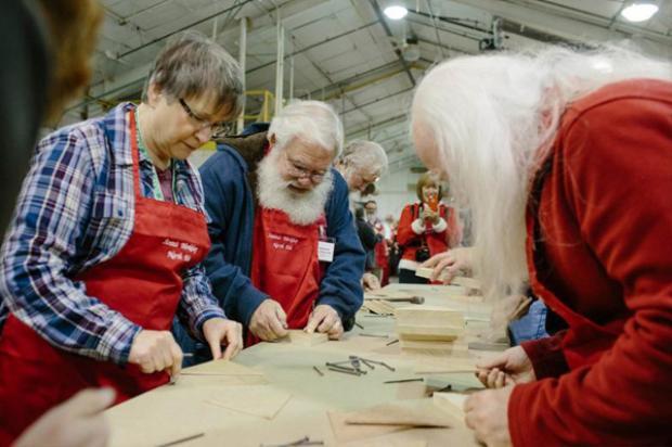 Các ông già, bà già Noel tương lai đang cặm cụi chế tạo đồ chơi bằng gỗ.
