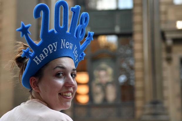 """Cô gái đội mũ có dòng chữ """"Chúc mừng năm mới 2018"""" tại thành phố Sydney, Australia."""