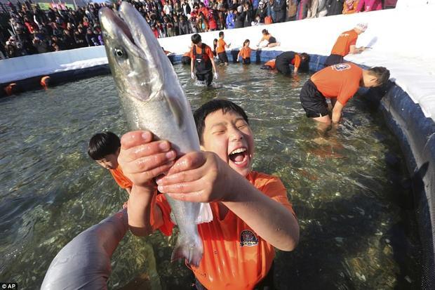 Một cậu bé đáng yêu reo lên vui sướng khi bắt được cá hồi. Cái rét thấu xương không thể khiến tinh thần lao động, vui chơi của các cô bé, cậu bé giảm đi.
