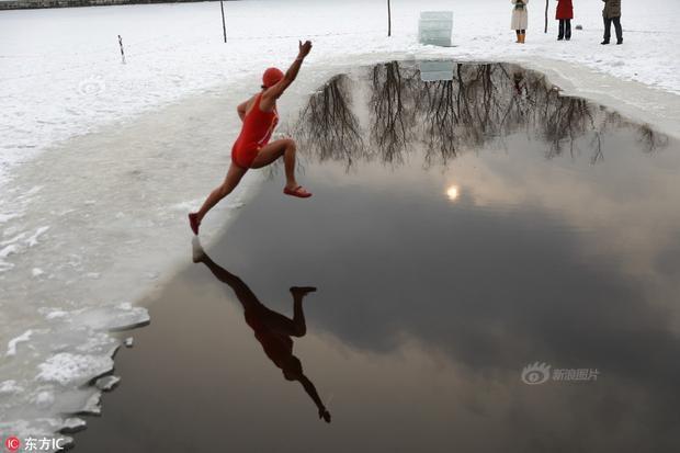 Cuộc thi thu hút sự tham gia của nhiều người, cả nam và nữ. Trong ảnh, người phụ nữ mặc bộ đồ bơi mỏng đang nhảy xuống dòng sông băng.