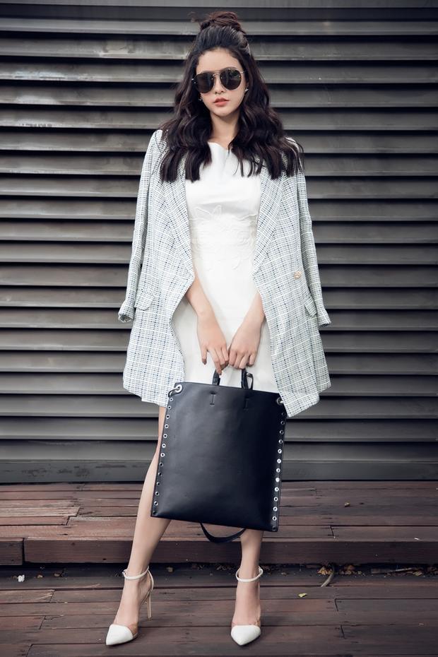 Với chiếc váy trắng đơn giản, Trương Quỳnh Anh lựa chọn cách khoác thêm măng tô ca-rô dáng dài bên ngoài nhằm tạo sự khác biệt.