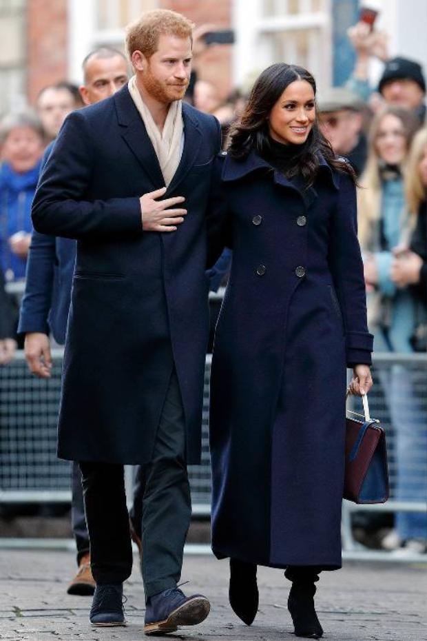 Phối hợp ăn ý với hoàng tử Harry, Meghan Markle diện áo choàng dài màu xanh thẫm, kết hợp với boot đen thanh lịch.