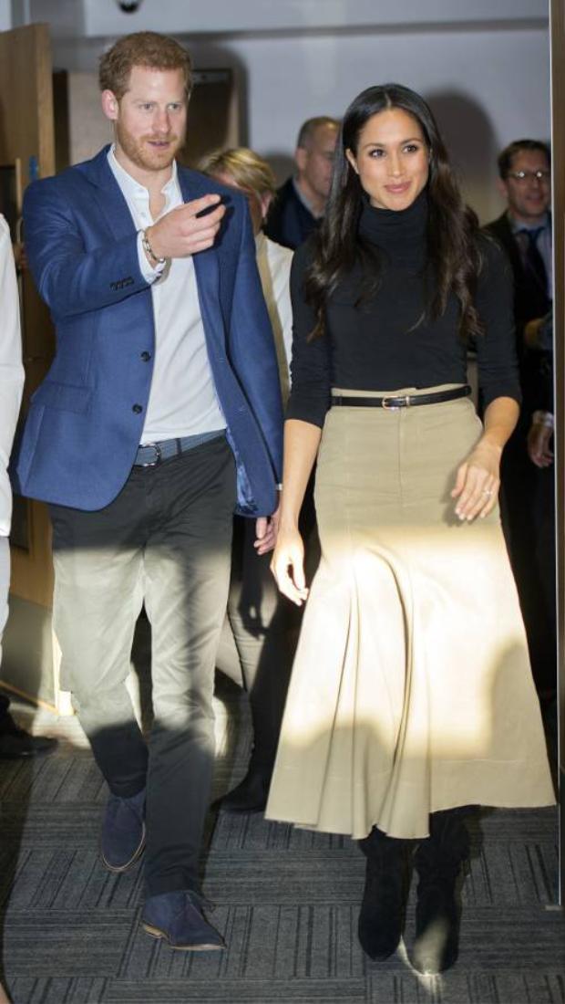 Ngay cả khi xuất hiện bên cạnh hoàng tử Harry, Meghan Markle vẫn đẹp một cách giản dị với chân váy màu camel và áo cổ lọ đen cực đơn giản.