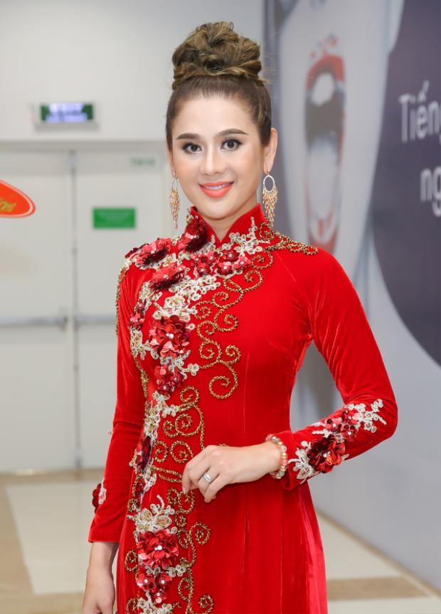 Cô dâu mới Lâm Khánh Chi trong sự kiện ra mắt phim cũng diện bộ áo dài đỏ rực rỡ, thêu hoa cầu kì.
