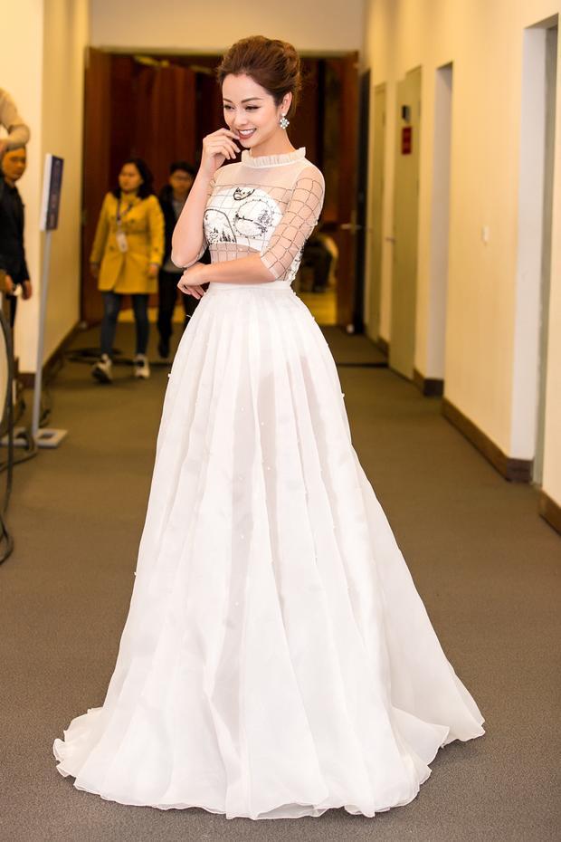 Như mọi khi, Jennifer Phạm chọn trang phục đầm dạ hội phong cách nữ tính, thanh lịch. Thiết kế tông trắng khá hợp vóc dáng người đẹp. Phần thân áo được thiết kế với chất liệu voan mỏng, phần vải che vòng 1 chỉ khoảng 1 găng tay nhằm tạo nét cuốn hút cho người mặc.
