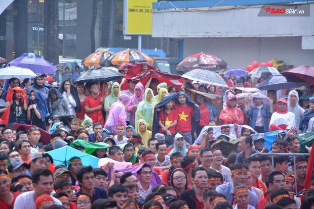 Cơn mưa nặng hạt khiến một số người phải sử dụng áo mưa, ô để tránh bị ướt.