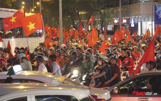"""Khắp các nẻo đường, đâu đâu cũng tràn ngập cờ đỏ sao vàng và những khẩu hiệu """"Việt Nam vô địch"""" vang dậy."""