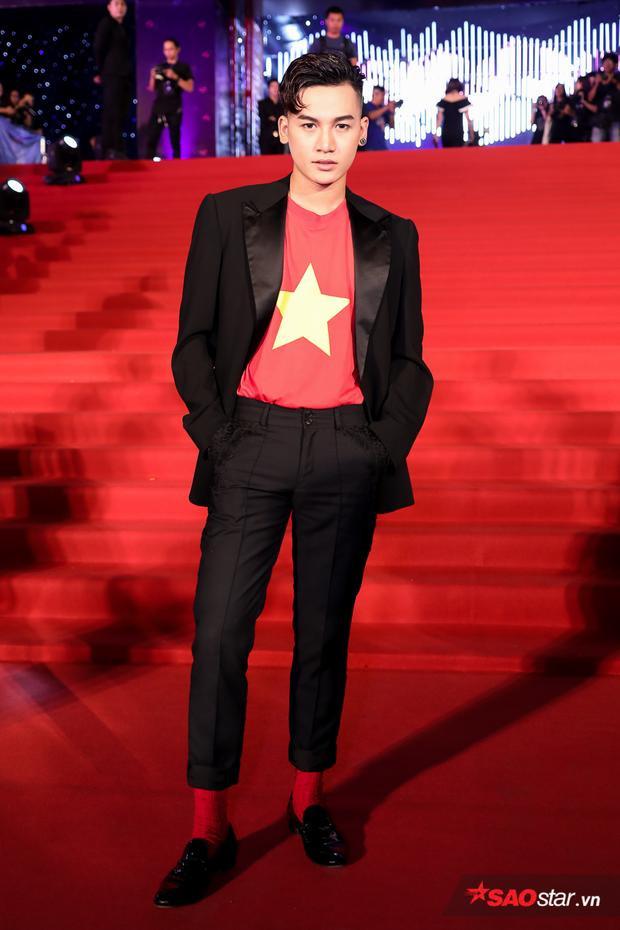 Ali Hoàng Dương diện áo in hình cờ đỏ - sao vàng, bên ngoài khoác vest đen đầy lịch lãm, sang trọng.