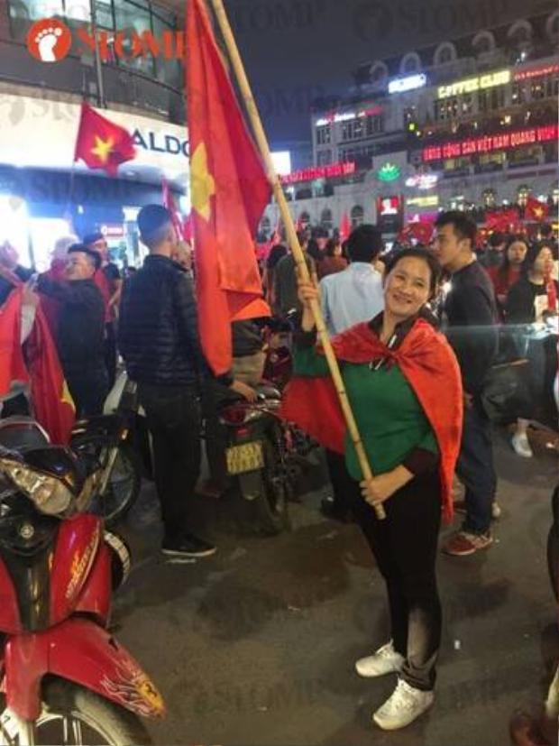 Một người phụ nữ đứng phất cờ tổ quốc giữa phố.