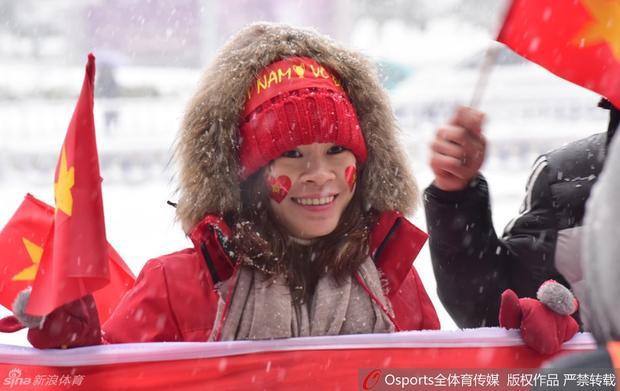 CĐV mặc áo khoác đỏ, đội mũ len màu đỏ, đi găng tay đỏ và cầm quốc kỳ để cổ vũ cho đội tuyển nước nhà.