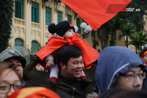 Em nhỏ cuốn Quốc kỳ được bố mẹ vác trên vai đi đón ĐT U23 Việt Nam.