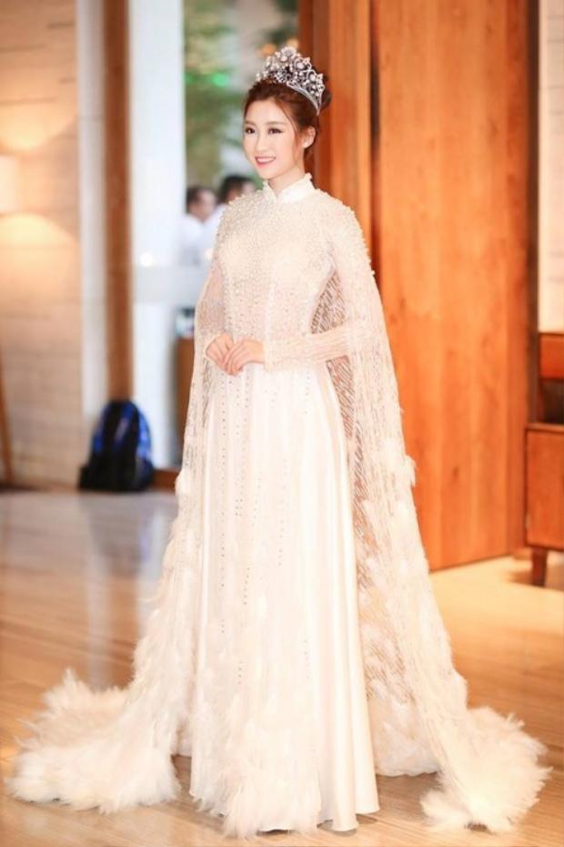 Thiết kế tông trắng lấy ý tưởng từ áo dài đem đến cho Đỗ Mỹ Linh vẻ nền nã, tao nhã. Chất liệu lông vũ cùng ren được sử dụng hợp lí, hoàn toàn nhẹ nhàng, thanh thoát.
