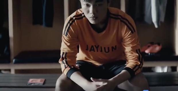 Sau đó chuyển cảnh anh chàng ngồi trong phòng thay đồ của cầu thủ.
