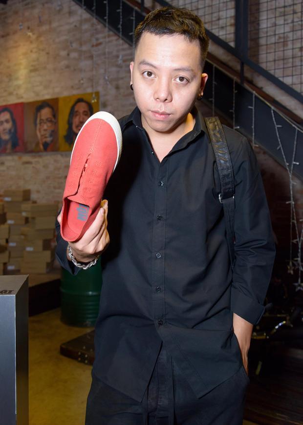Hoàng Touliver đến sự kiện với bộ trang phục tông đen. Anh hào hứng chọn đôi giày tông đỏ nổi bật để kết hợp cùng set đồ tối màu.