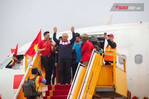 Huấn luyện viên Park Hang Seo là người đầu tiên bước ra ngoài máy bay, giơ tay vẫy chào người hâm mộ.