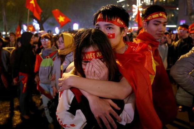 Cổ động viên ở Hà Nội buồn bã khi đội tuyển để thua vào phút chót trong trận chung kết với Uzbekistan. Ảnh: Reuters