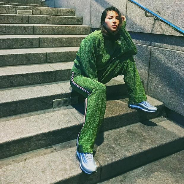 """Với set đồ thể thao màu xanh lá có ánh nhũ đã giúp Minh Triệu """"nổi bần bật"""" giữa đường phố. Siêu mẫu quả thực vô cùng thông minh khi không quá cầu kì trong kiểu dáng của quần áo mà chú trọng hơn vào cách phối hợp màu sắc."""