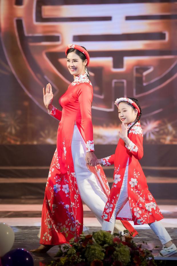 Diện tà áo dài đỏ in hoa nhí, hoa hậu Ngọc Hân dắt tay người mẫu nhí, hân hoan chào, vẫy tay khán giả.
