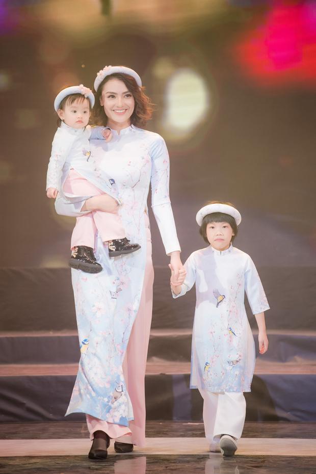 Người mẫu Hồng Quế cũng bế con gái Cherry lên sân khấu, đem đến không khí mới mẻ, thú vị cho show diễn.
