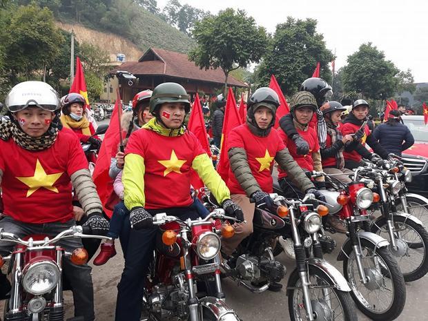 Một nhóm cổ động viên đi xe máy đứng dọc đường lối vào nhà Xuân Trường.
