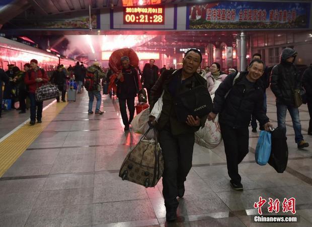 """Vừa mới bước qua ngày 1/2, người dân đã nườm nượp kéo nhau về quê ăn Tết. Ảnh chụp lúc 0h52 phút ngày 1/2 tại ga Bắc Kinh, trên tuyến đến Trùng Khánh. Đoạn đường nối Bắc Kinh - Trùng Khánh dài tới 1.982km, cuộc """"di cư"""" sẽ kéo dài 28 tiếng đồng hồ qua 12 trạm dừng chân."""