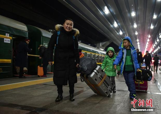 Một người mẹ cùng với hai con lỉnh kỉnh đồ đạc chuẩn bị lên tàu về quê.