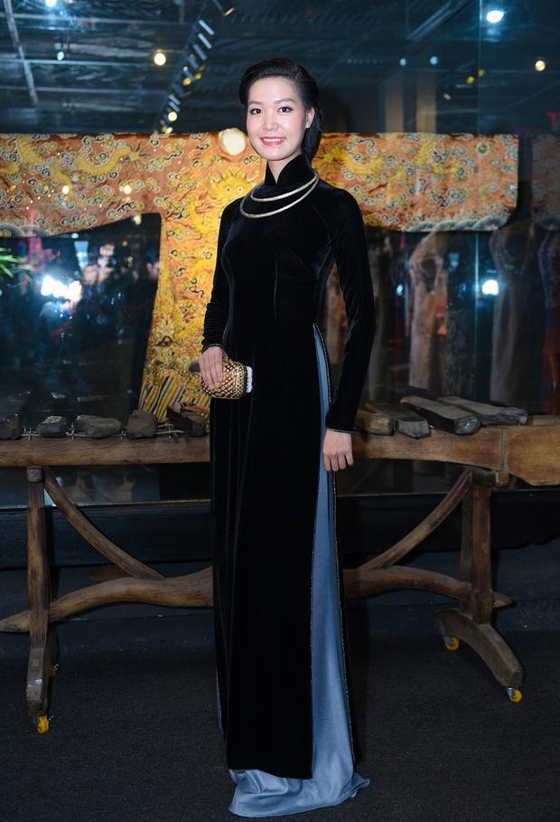 Có vẻ như áo dài đen chất liệu nhung được dàn sao ưa chuộng hơn cả. Hoa hậu Thùy Dung cũng chọn có mình bộ áo dài đen tuyền nền nã khi tham gia sự kiện. Kiểu tóc buộc thấp của cô gợi nhắc đến hình ảnh những thiếu nữ Hà Nội thời xưa. Sử dụng kiềng bạc, Thùy Dung trở nên đài các và thu hút.