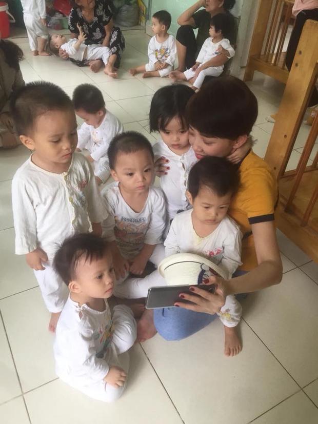 Các em nhỏ không có khoảng cách, vây quanh Tóc Tiên để xem điện thoại.
