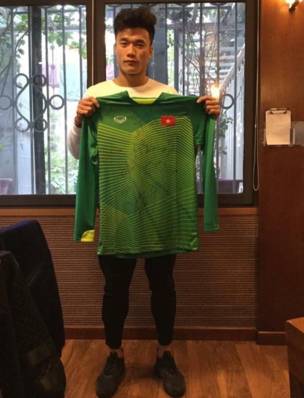 Thủ môn Bùi Tiến Dũng chụp cùng chiếc áo có chữ ký của các cầu thủ U23. Ảnh: Dân trí