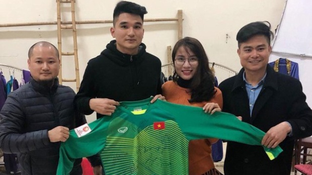Trung vệ Lê Văn Đại trao chiếc áo cho người đại diện trúng đấu giá. Ảnh: Dân trí