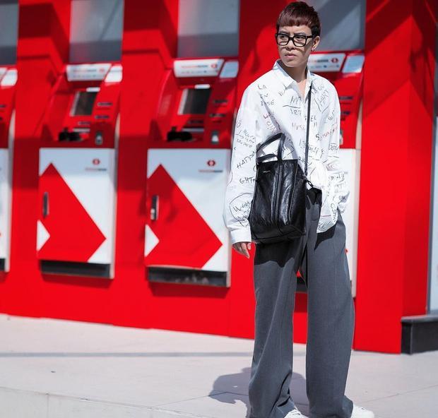Stylist Huy Mạch xuống phố với set đồ độc, lạ gồm áo sơ-mi phom rộng in họa tiết chữ cái và quần ống suông. Chiếc túi da bóng đeo chéo làm điểm nhấn khiến set đồ trở nên hoàn hảo.