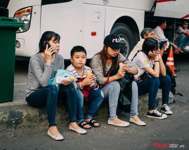 Nhiều người tranh thủ ăn tạm ổ bánh mỳ lót dạ trước khi lên xe về quê.