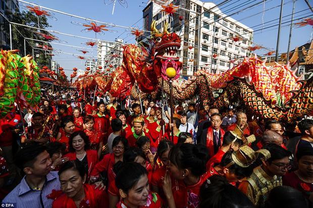 Các nghệ sĩ biểu diễn tiết mục múa rồng đang đi diễu hành quanh khu phố Tàu ở Yangon, Myanmar.
