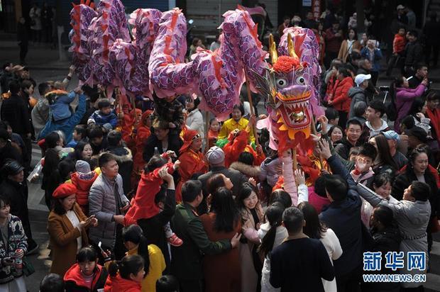 Khi đội múa rồng đi qua, người dân cố gắng chạm vào đầu rồng để lấy may.