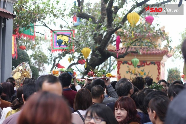 Đường đông nên mọi người phải đội lễ lên đầu, di chuyển chậm chạp.